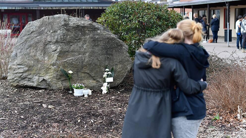 två tjejer som kramas vid minnesplats vid stor sten