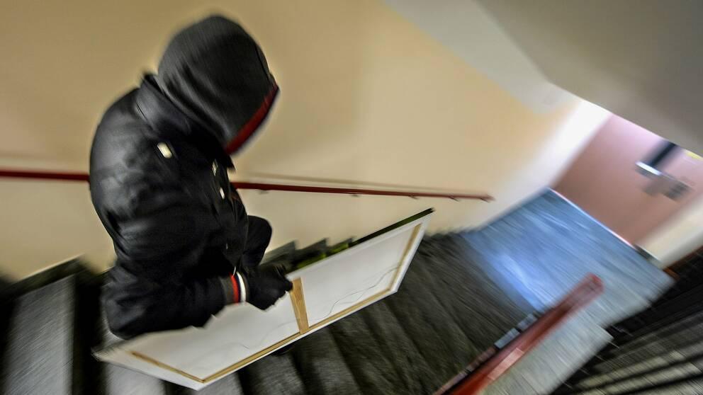 man med huva springer i ett trapphus med en tavla