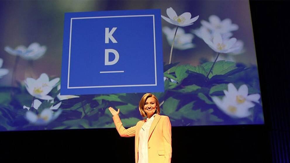 """Ebba Busch Thor framför en bild på logotypen; En blå fyrkant med bokstäverna """"KD"""" ovanför ett streck."""