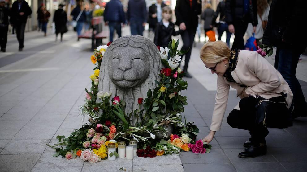 En kvinna lägger ned blommor vid ett betonglejon på Drottninggatan.