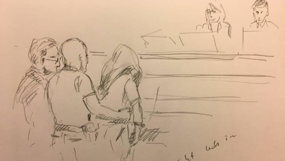 39-åringen fördes in i rättssalen (längst fram till höger i raden av tre på denna teckning) med huvudet täckt.