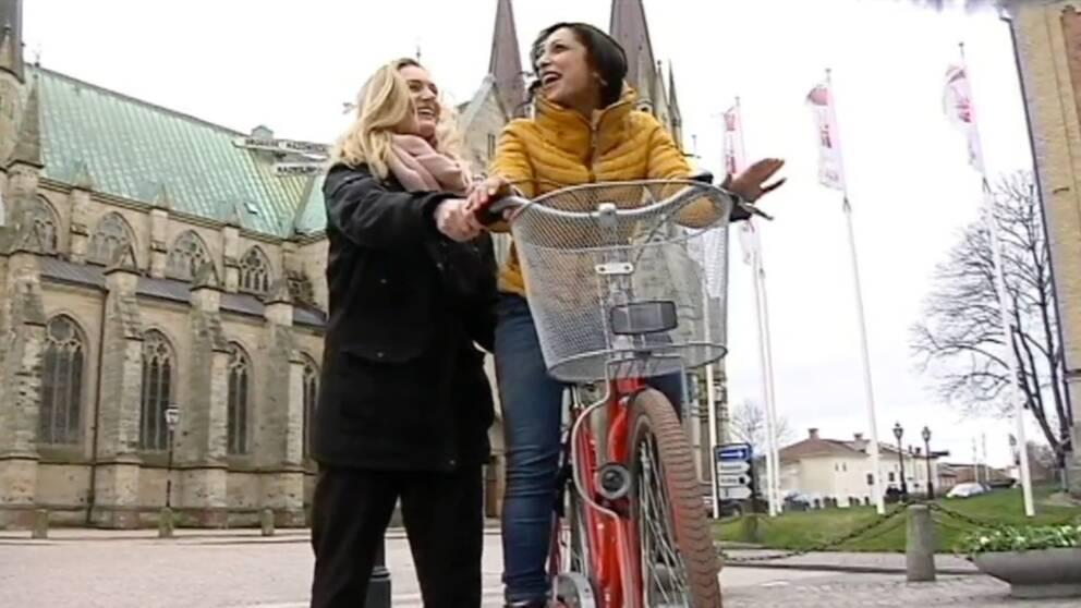 vuxen tjej på cykel lär sig cykla och får stöd av annan tjej