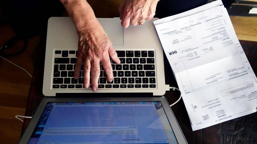 Kvinna betalar räkning via datorn