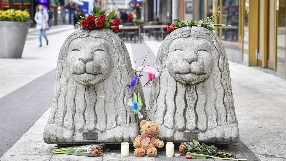 Två betonglejon på Drottninggatan, de har rosor på huvudena och blommor framför sig