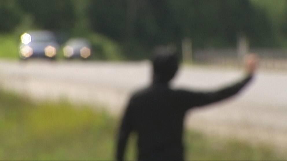 Anonym och suddig bild bakifrån, en svartklädd person viftar åt två bilar som kommer körande mot personen.