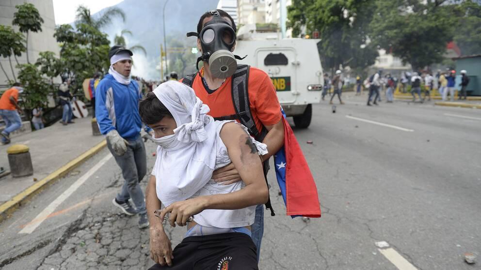 Mannen fick hjälp av en annan demonstrant, som släpade honom i säkerhet.