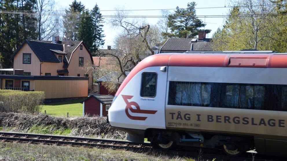 Passageratåg passerar framför villor.