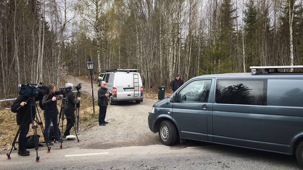 pressfotografer filmar man som pratar på grusväg i skog, polisens bilar