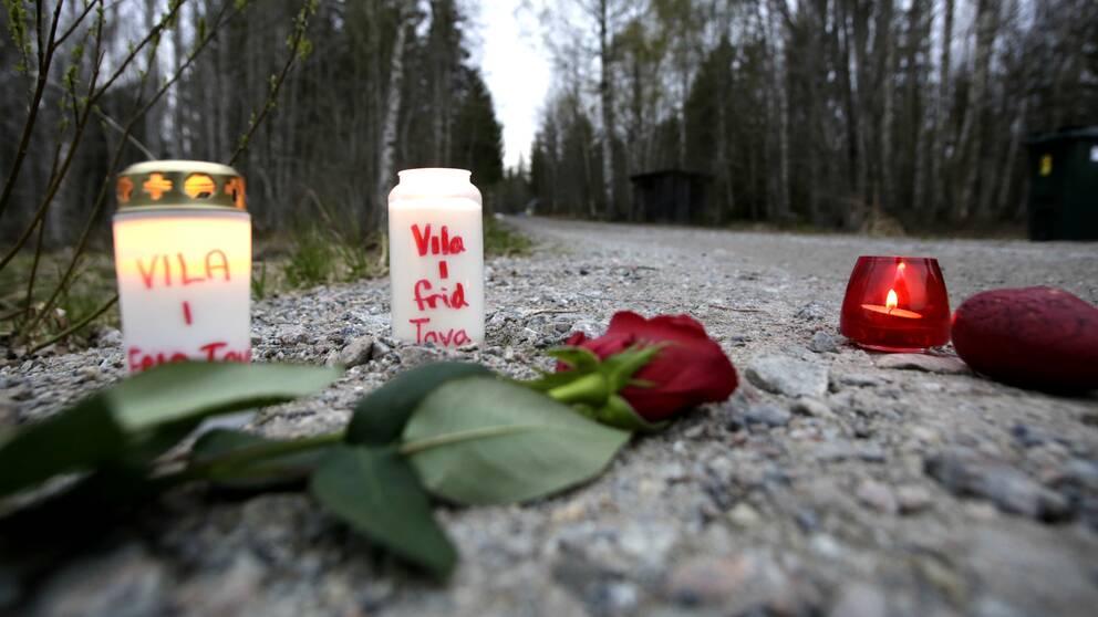 Tända gravljus och en ros i vägkanten