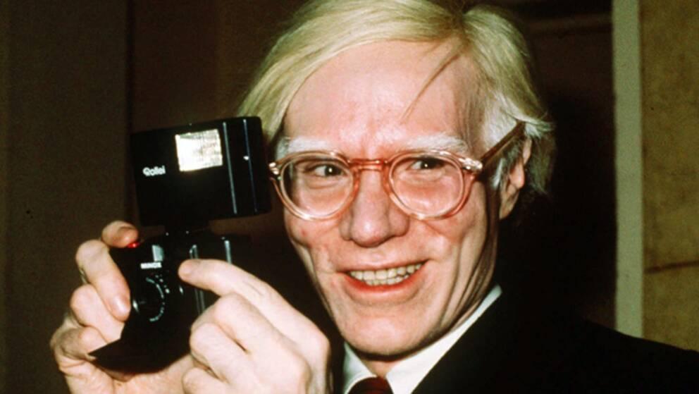En leende Andy Warhol 1976, iklädd kostym och glasögon med en kamera i händerna.