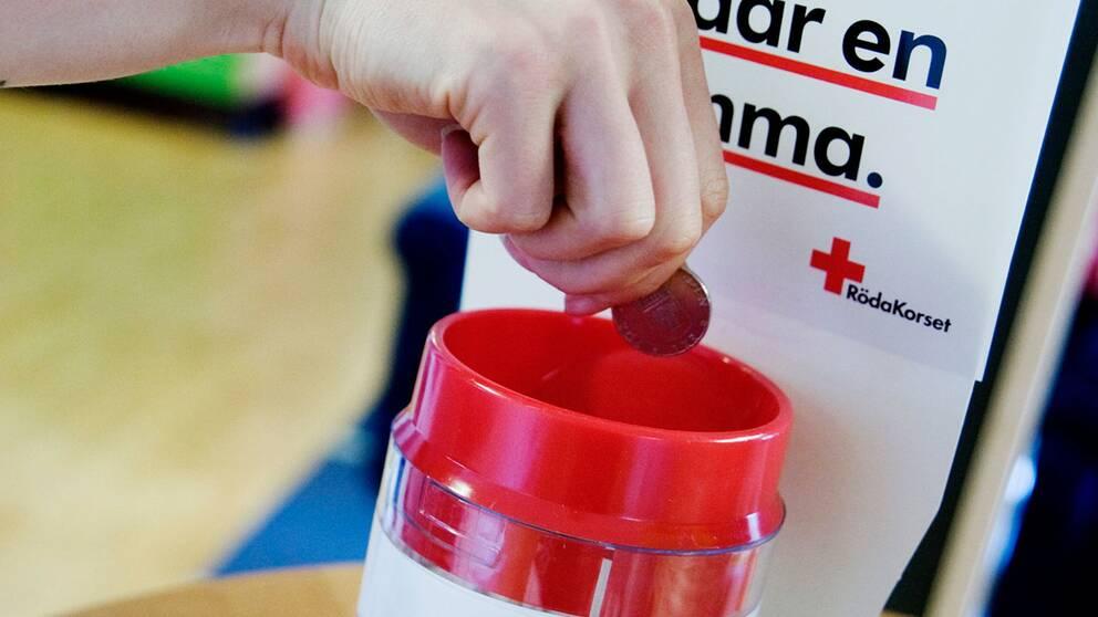 En hand lägger mynt i en insamlingsbössa för Röda korset.