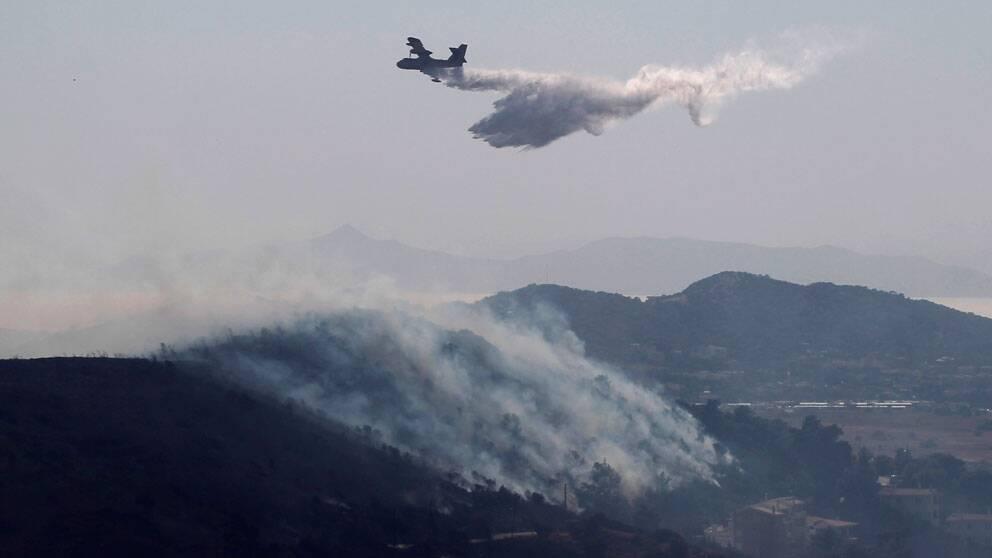 Ett brandbekämpningsplan vattenbombar en brand söder om Atén