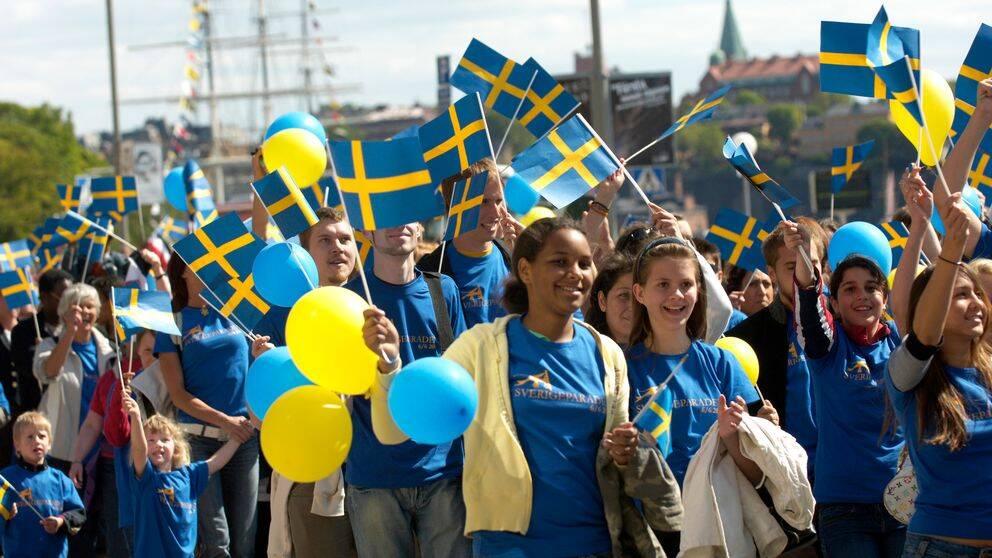 Sveriges nationaldag firas runt om i landet. Arkivbild från Skansen i Stockholm. Barn firar med flaggor och ballonger.