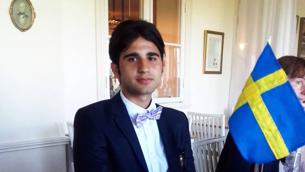 Jakob Ashour som fått svenskt medborgarskap sitter bredvid en svensk flagga.