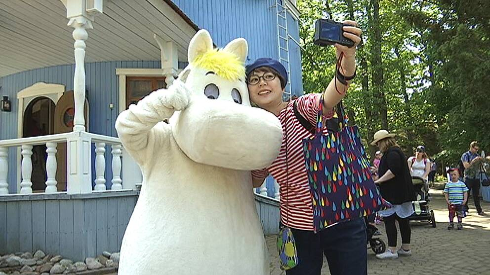 Mumintroll poserar tillsammans med en människa framför en kamera
