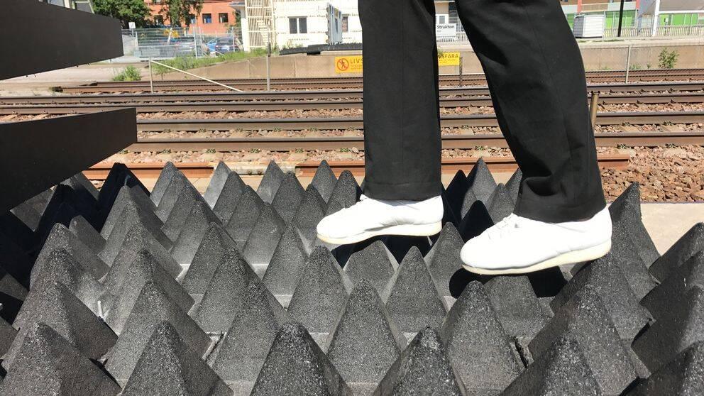 fötter går på pyramidformade gummimattor vid järnvägsspår