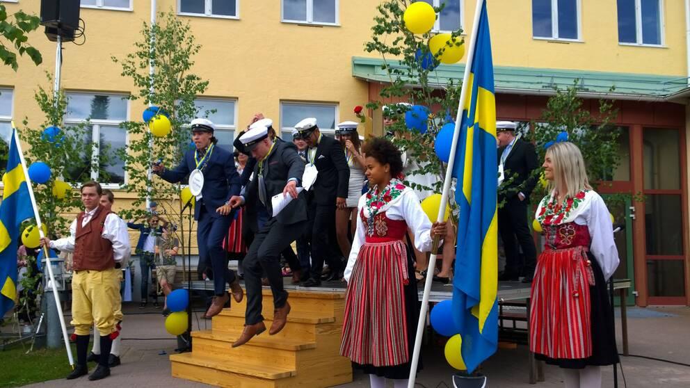 Ett gäng studenter står samlande med studentmössor på. Ballonger och Sverigeflaggor pryder scenen de står på.