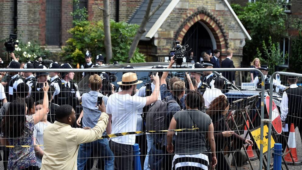 Premiärminister Theresa May eskorteras iväg från Kensington samtidigt som demonstranter vrålar ut sin vrede