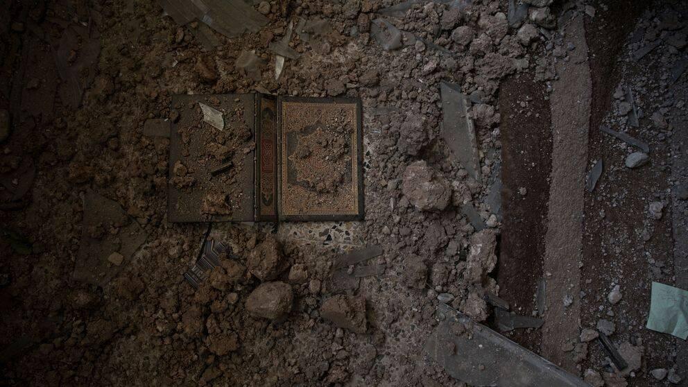 Aisam söker sin koran, han hittarden slängd under ett bord, täckt av damm och sprängmedel.