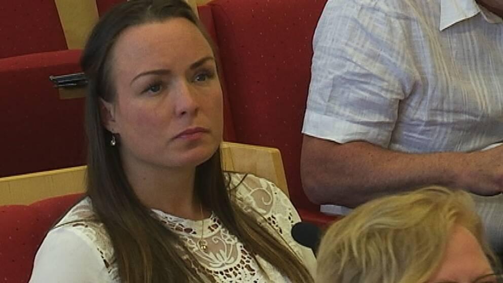 Linda Larsson syns titta bortåt. Hon sitter på en röd stol.