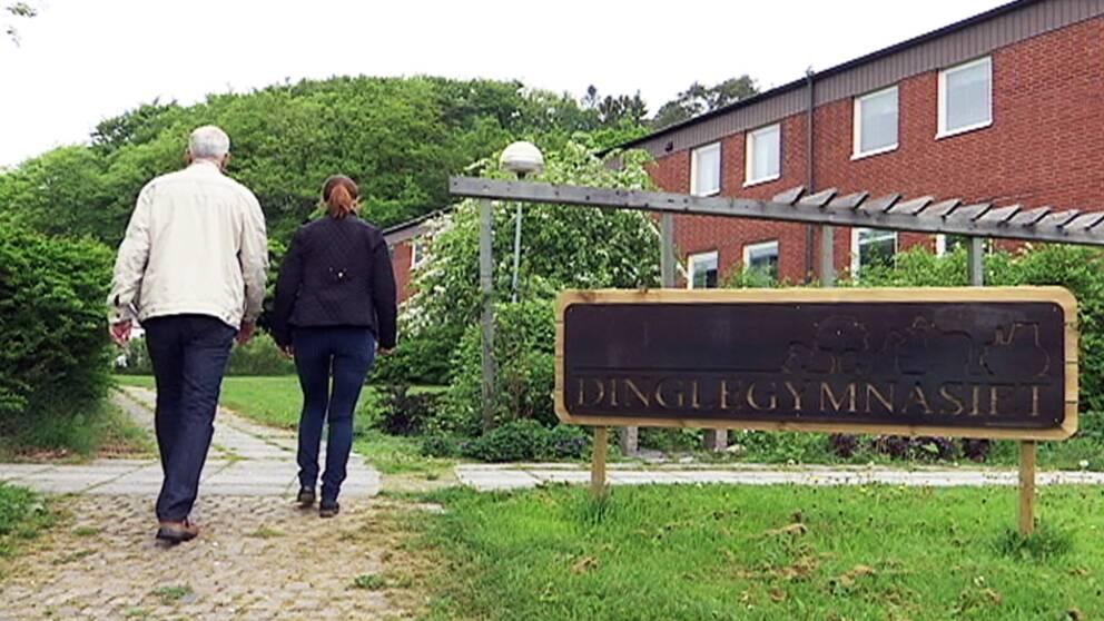 Två personer går med ryggen mot kameran intill en skylt som det står Dinglegymnasiet på