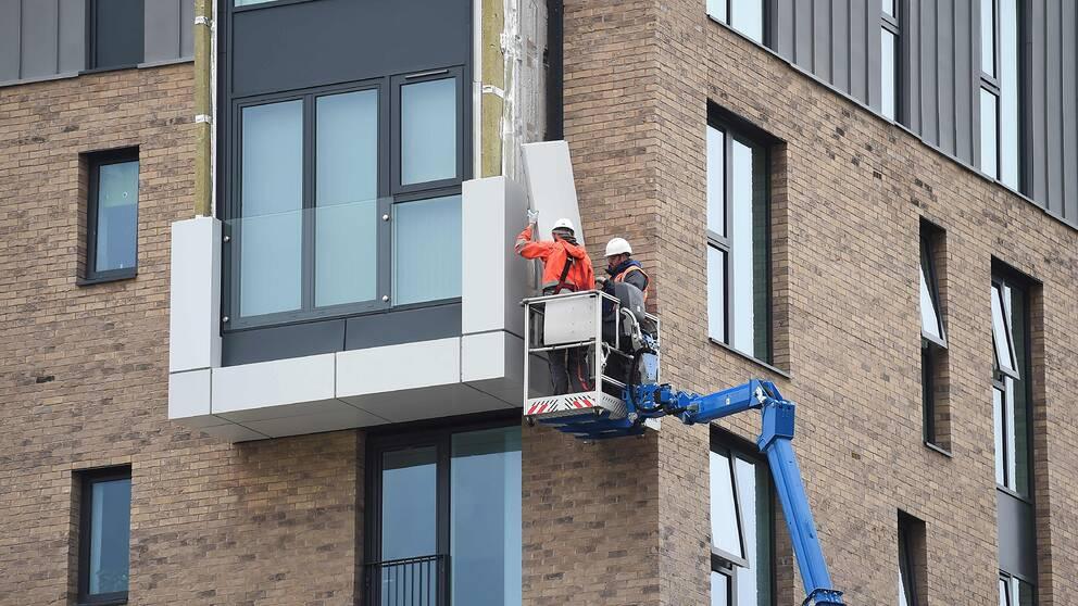 Arbetare plockar bort fasadmaterial från en byggnad i Wythenshawe i Manchester.