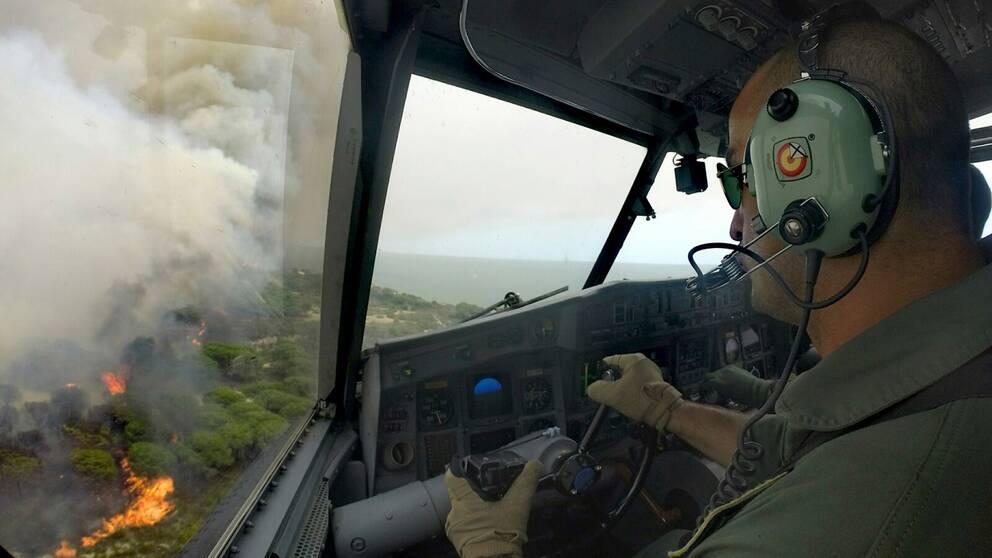 Ett spanskt brandflygplan flyger över skogsbranden i södra Spanien.