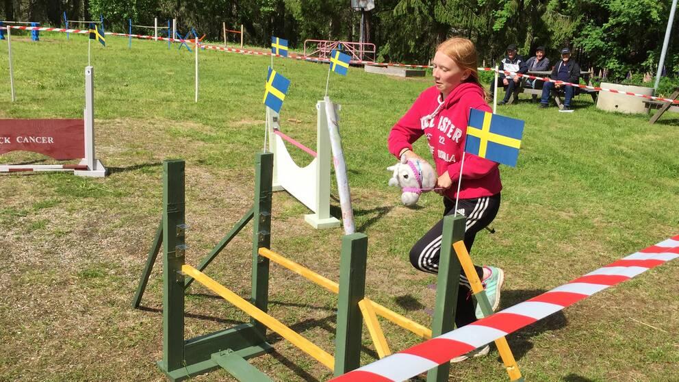 Minna Söderlund från Töva hoppar hinder med käpphäst.