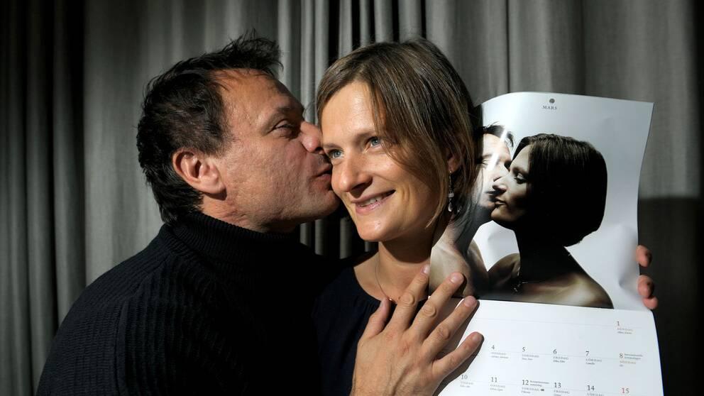 """Michael Nyqvist och frun Catharina Nyqvist Ehrnrooth som visar 2009 års version av kalendern """"Svenska Kalenderflickorna med kalendermän 2009""""."""