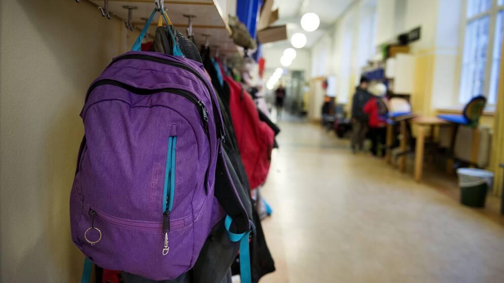 Korridor i en skola, väskor och kläder som hänger på klädhängare.