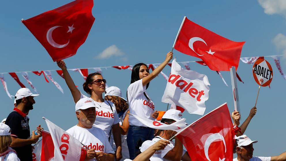 """Människor vinkar med turkiska flaggor under ett möte för att markera slutet på den oppositionsrepublikanska folkpartiets (CHP) ledare Kemal Kilicdaroglus 25-dagars protest, kallad """"Rättvisemarschen""""."""