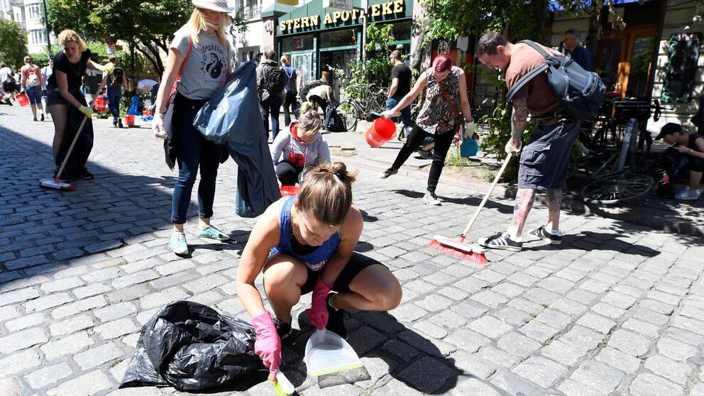 En kvinna sitter på knä med en lite sop i händerna och gör rent på kullerstensgatan.