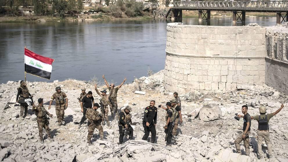 Irakiska specialstyrkor firar att de nått fram till floden Tigris västra strand, där Mosuls gamla stad ligger. Förödelsen i staden är enorm.