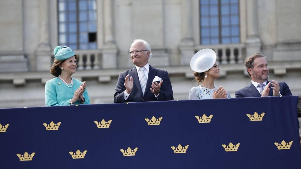 Drottning Silvia, kung Carl Gustaf, prinsessan Madeleine och Christopher O'Neill ser på födelsedagskortegen från Logården.