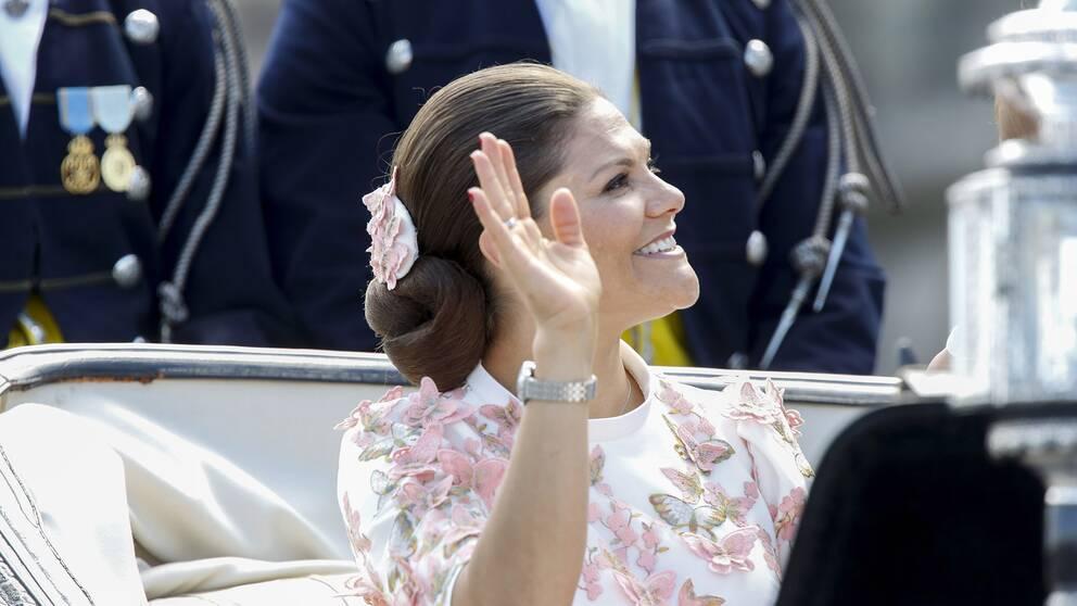 Kronprinsessan Victoria i vagnen under kortegen, vinkandes till tusentals åskådare.