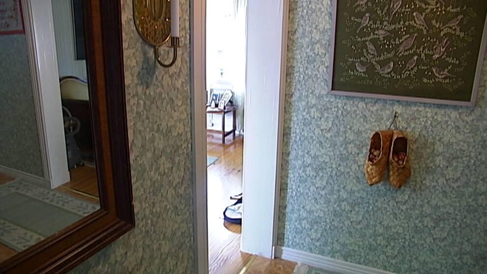 Ett rum med en blommig tapet och ett par nävertofflor hänger på en vägg.