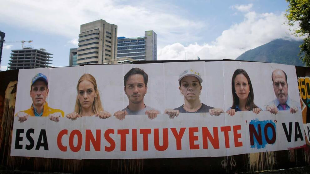 """Bild på affisch på ett plan framför några höghus. På affischen ses sex oppositonsledare med en skylt där det står """"Esa constituyente no va""""."""