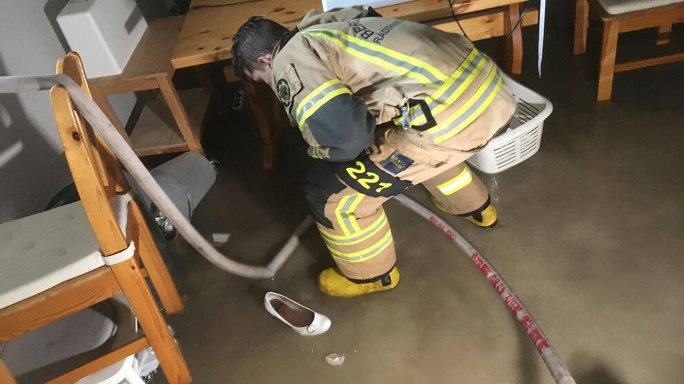 Brandman pumpar ut vatten ur källare.