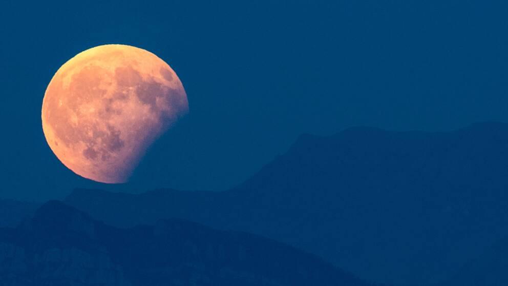 Den partiella månförmörkelsen syns här vid alperna i Schweiz.