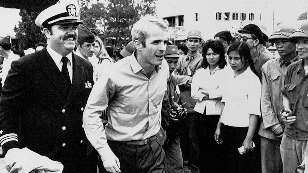 John McCain stöttas av en officer efter att ha blivit frisläppt.
