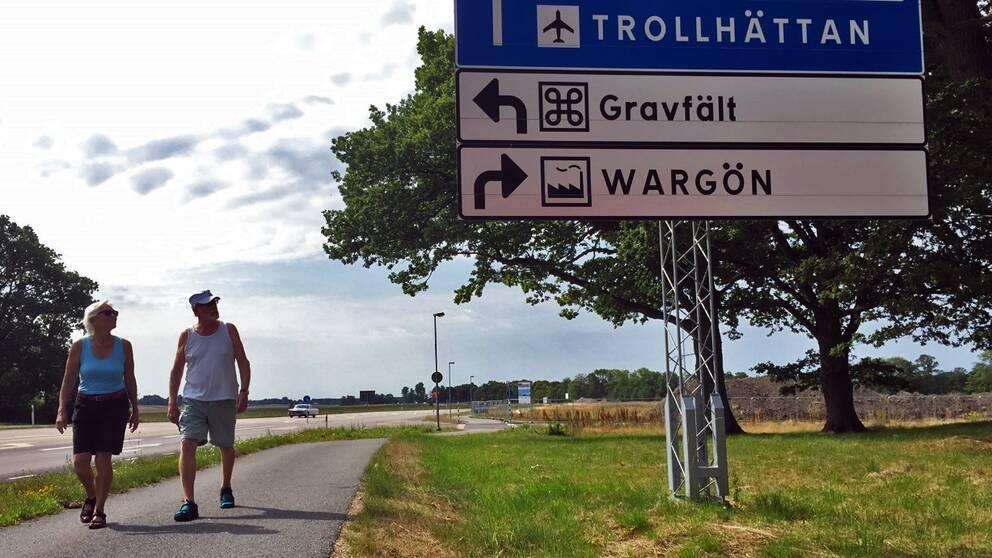 Två personer på en gångväg intill en skylt som pekar mot Wargöns industriområde