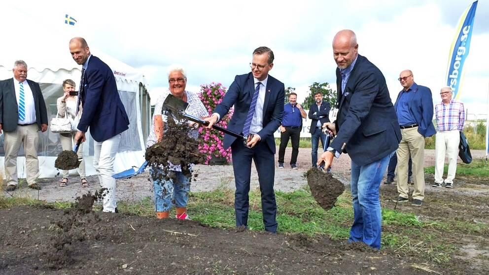 Fyra personer med varsin spade kastar jord