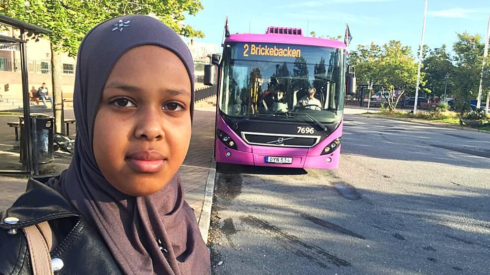 Salma Osman i förgrunden och en buss i bakgrunden