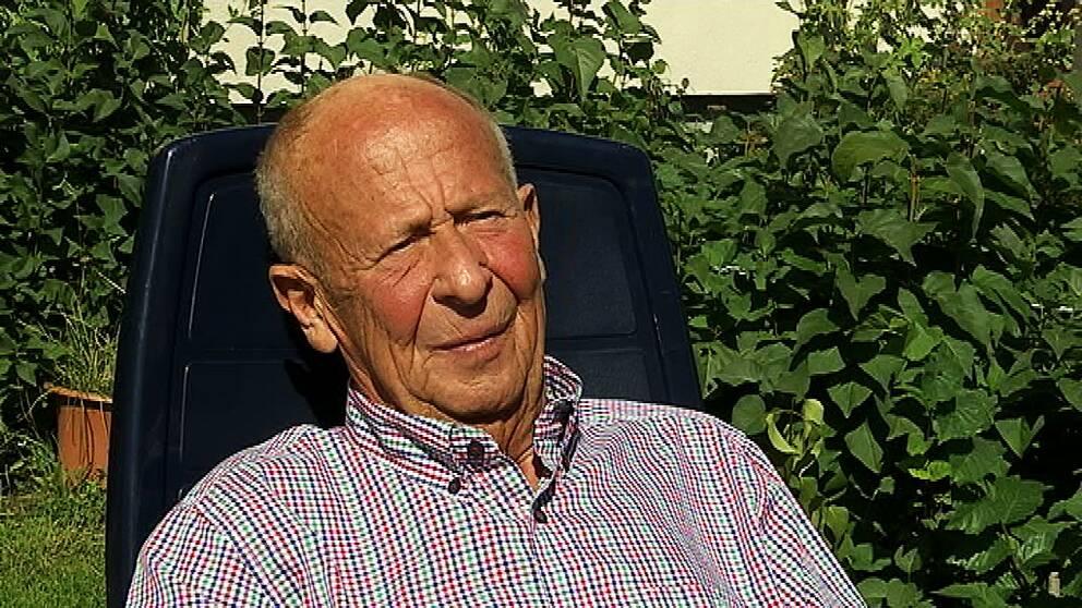 Arne Carlsson, en man, sitter i rutig skjorta ute i solen och tittar snett bredvid kameran.
