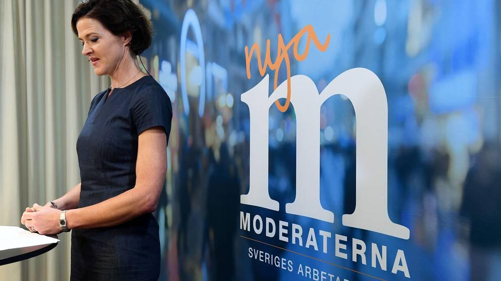 Anna Kinberg Batra framför en Nya Moderaterna-logga.
