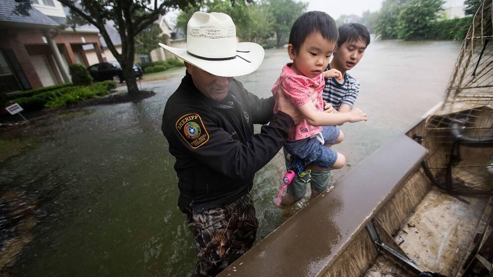 Sheriff Troy Nehls och Lucas Wu hjälps åt att lyfta upp Ethan Wu i en båt. Bilden är tagen i Fort Bend County, Texas.
