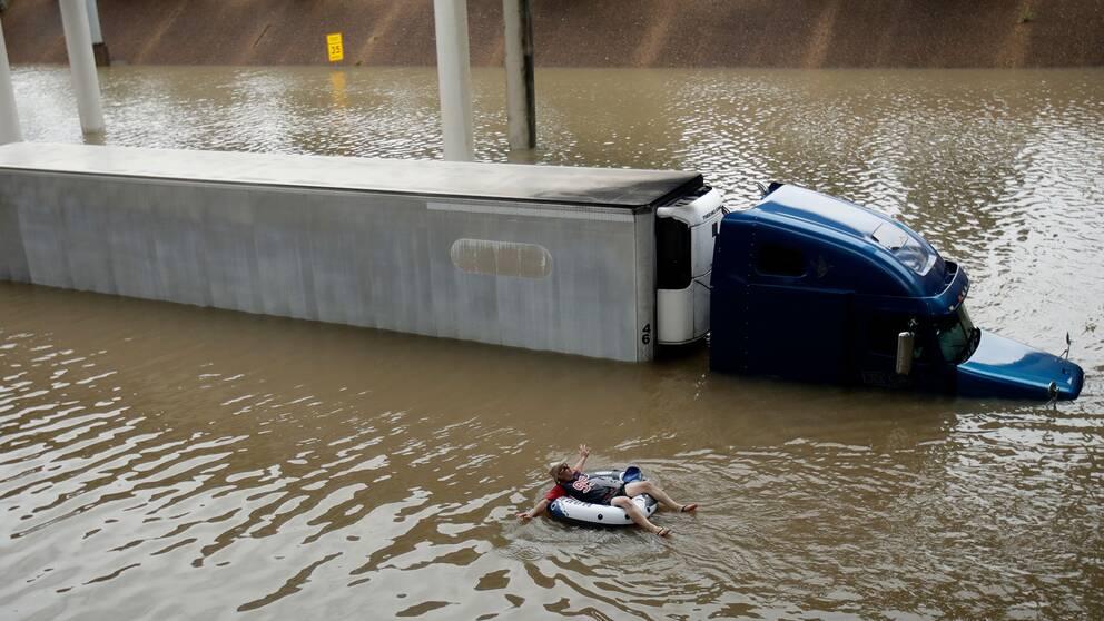 En man flyter nedför en översvämmad motorväg i centrala Houston i en badring.
