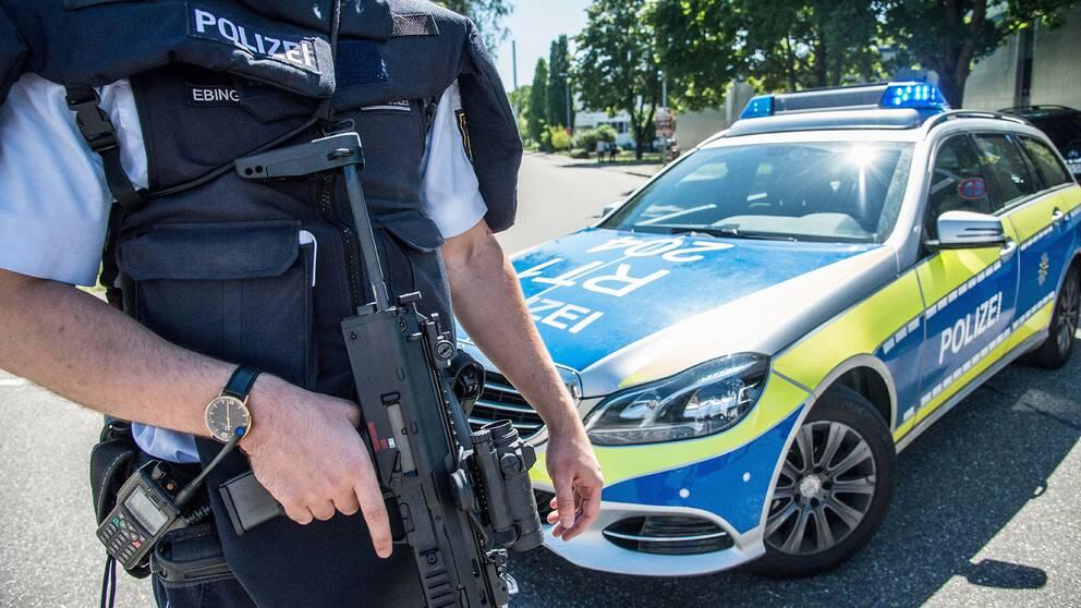 En polis står med ett automatvapen vid en polisbil.