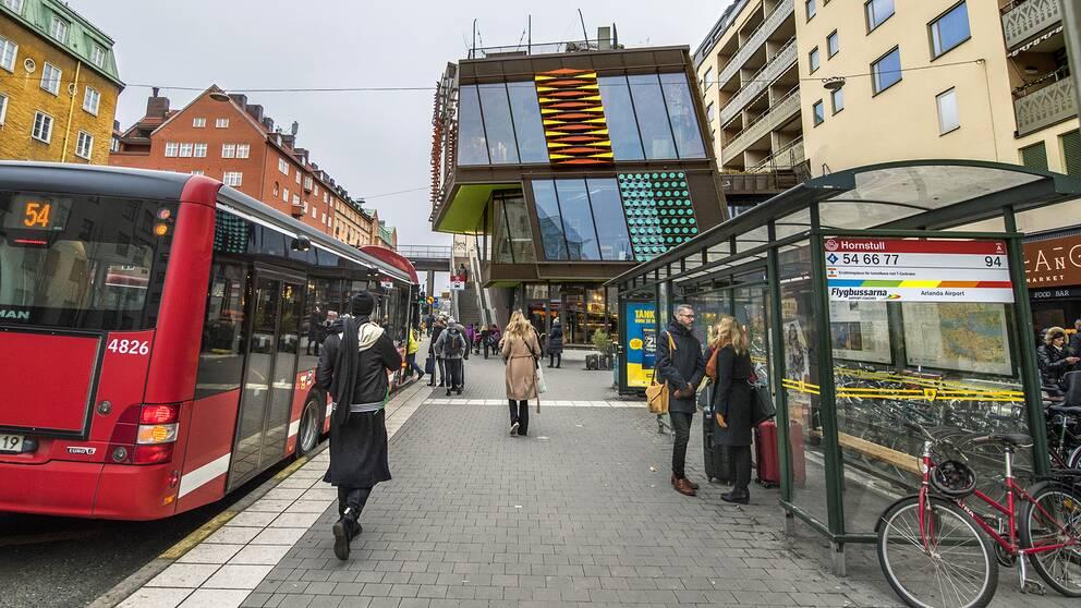 En buss och personer vid en busshålllsplats.