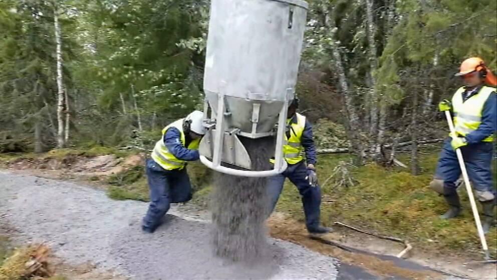 två personer i arbetskläder och hjälm styr behållare som släpper grus